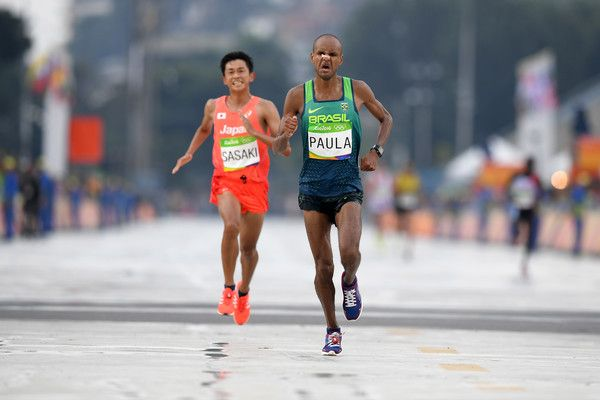 Paulo Roberto Paula of Brazil and Satoru Sasaki of Japan cross the line during the Men's Marathon on Day 16 of the Rio 2016 Olympic Games at Sambodromo on August 21, 2016 in Rio de Janeiro, Brazil.