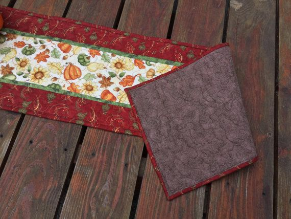 Fall Table Runner, Fall Quilted Table Runner, AutumnTable Runner, Maple Oak Leaf Runner, Sunflowers Pumpkins Table Runner, Rust Green Orange  This Fall quilted table runner is ready for your table or buffet. It has a center with sunflowers, oak and maple leaves, squash, acorns and pumpkins on a cream background. It has a thin border in green. The outer border is a print with maple and oak leaves in green, along with little vines and berries in yellow, green and orange on a rust colored…
