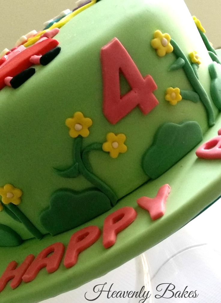 Side view of Peppa Pig Birthday cake with flowers and bushes. facebook://heavenlybakesaltona
