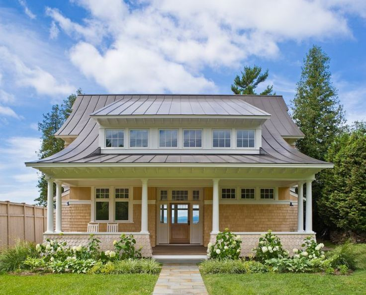 A concave metal roof on a house. Curved-in standing seam panels on a cottage.