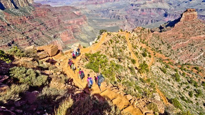 An aerial view of the Headings family heading deep into the Grand Canyon carrying their paralysed grandfather and his wheelchair. Don't miss their truly inspirational story at: http://www.suitcasesandstrollers.com/interviews/view/hiking-grand-canyon-with-kids-wheelchair?l=all #GoogleUs #suitcasesandstrollers #travel #travelwithkids #familytravel #familyholidays #familyvacations #hiking #wheelchairs
