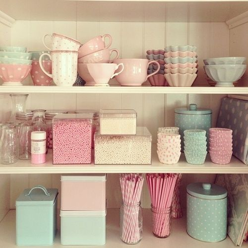 Pastel dishes, teacups, and vintage retro cupcake ephemera on shelves. Looks like *someone* went to town at Anthropologie and the baking supply store. :p