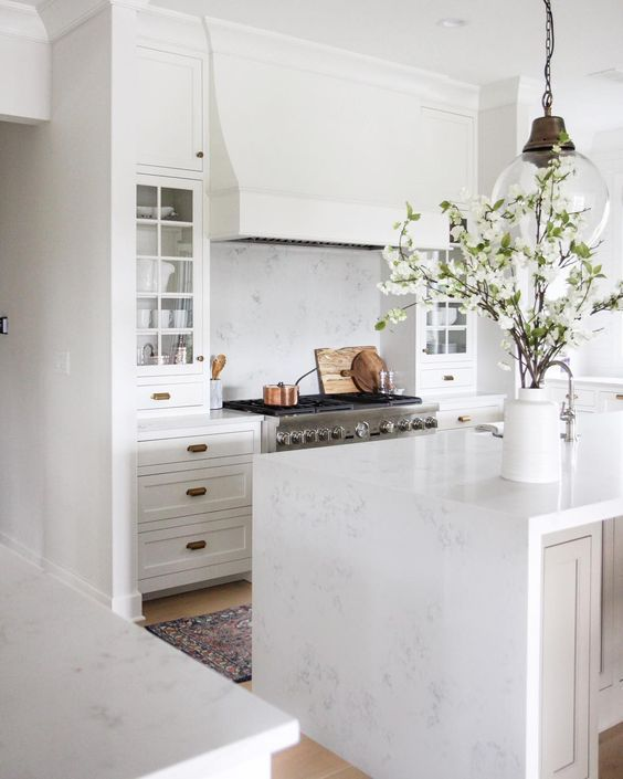 with marbled countertop and white kitchen cabinets