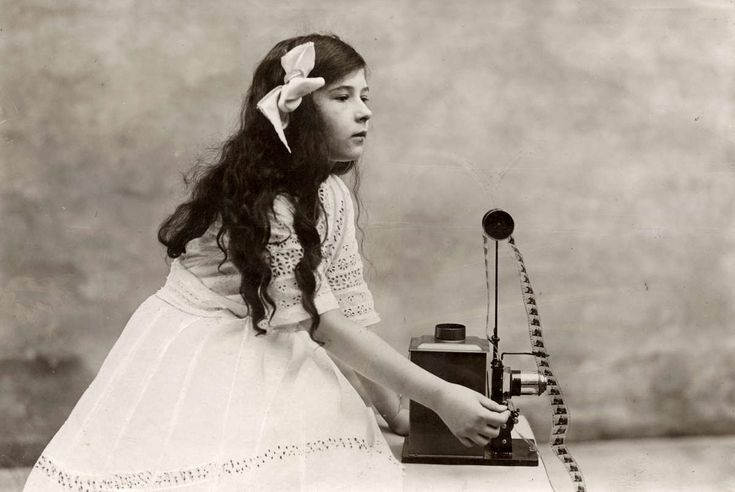 Een meisje met lang donker haar in een witte jurk met een kinematograaf/cinematograaf: een filmprojector.[Duitsland].1912.