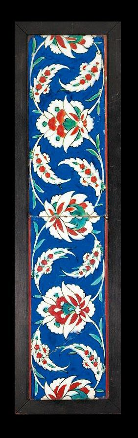 TWO IZNIK POLYCHROME POTTERY BORDER TILES, TURKEY, CIRCA A.D 1570-80 decorated in bole-red and green outlined in black with lotus-palmettes on arching stems with attached saz leaves on a brushed cobalt-blue ground 27 by 12cm. each; framed