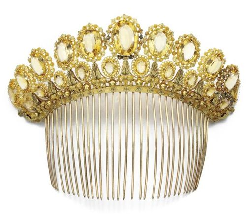Citrine Tiara Comb,1830, has French import marks and two rows of citrines in graduating sizes. The stones are clean, translucent, and well matched in color. The first row of stones is supported by a bridge of brass leaves separated by balls, which attaches to the comb with a floral applique.