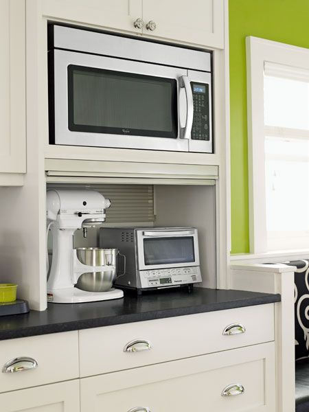A niche for the microwave gives it a built-in look. The custom appliance garage has its own outlets and a stainless-steel roll-down door. | Microwave: @whirlpoolusa: Appliances Garage, This Old House, Built In, Black Countertops, Appliance Garage, Kitchens Appliances, Houses Appliances, Photo, Storage Ideas