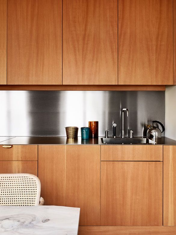 neat and clean stainless steel back-splash accents sleek cabinet doors--without handles