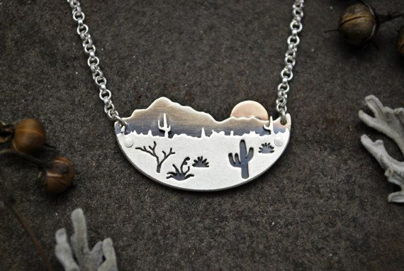This unique metalwork necklace features a gold sun rising over a tranquil desert landscape. Fabricated from sheets of silver and gold, all elements are cut by hand with a saw and layered together. The pendant is oxidized to silhouette the delicately pierced plants and contrast the mountains. An ombre finish accentuates the mountains with a highlighted ridge line.  Completed with a durable sterling silver chain that is made in the United States. Handmade diamond shaped links add a charming…