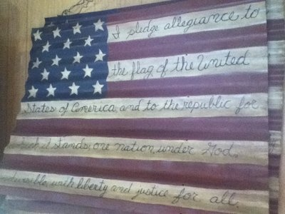 Flag painted on old barn tin with the words of the Pledge of Allegiance.