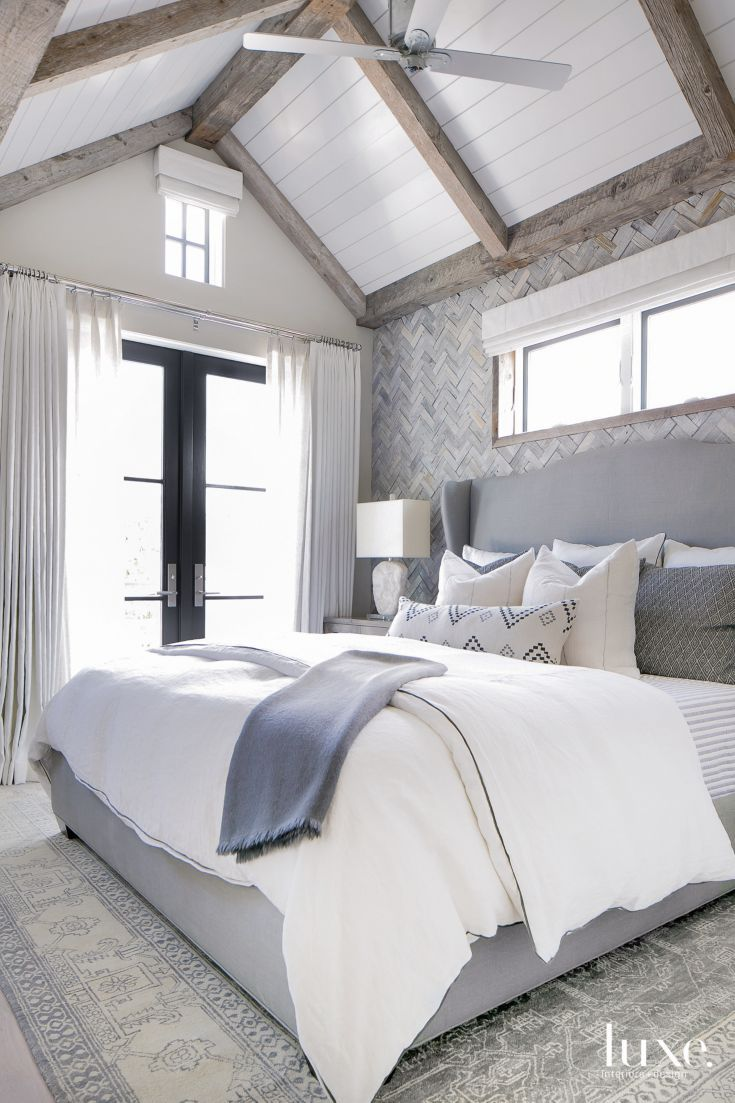 Reclaimed wood tiles from Famosa, set in a herringbone pattern, provide a rustic-chic backdrop for the master bedroom's custom bed, which is upholstered in fabric from C&C Milano. Draperies in Triangulated by Christopher Farr Cloth frame doors by Generations Finish Carpentry.