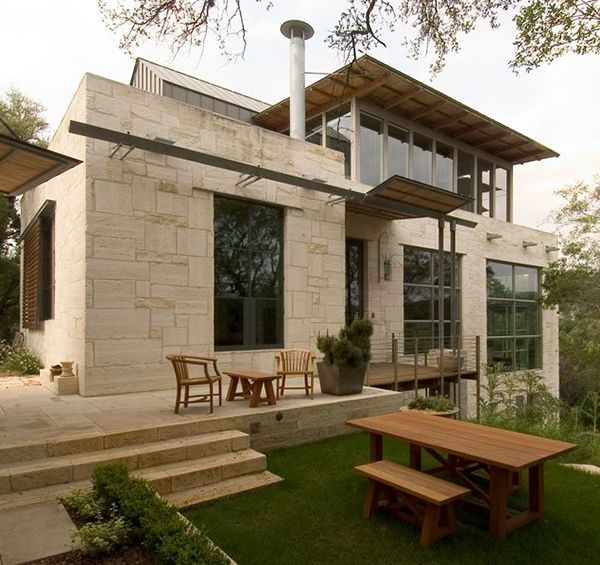 Rustic stone home with country kitchen and glass bath    Austin, Texas-based architecture firm Mell Lawrence Architects designed this rustic house right in their own backyard. Designed as an earthy sanctuary, this stone home design follows the lay of the sloped site with a layered layout both indoors and out.