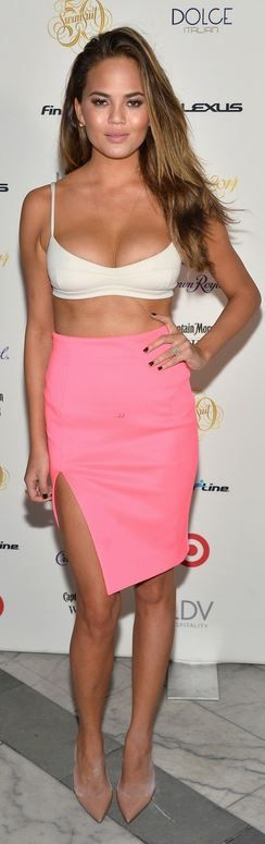 Who made Chrissy Teigen's white cropped top, pink skirt, jewelry, and nude pumps that she wore in Miami on February 20, 2014?