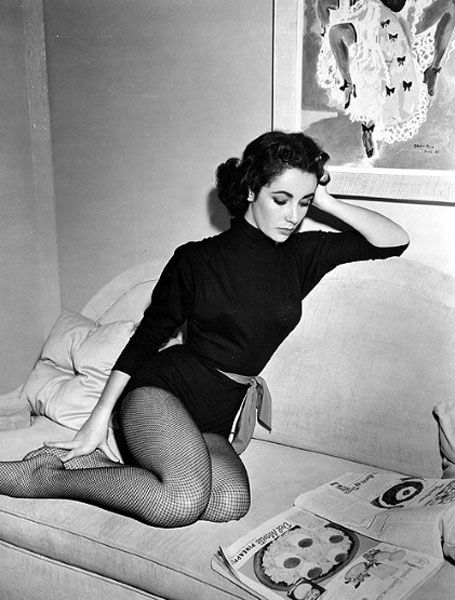Elizabeth Taylor, lounging in fishnet tights and a turtleneck onesie.  you know, like you do.