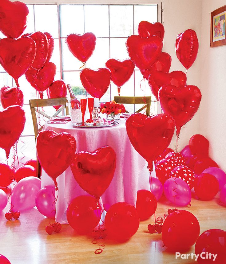 Looking for Valentine's Day ideas? Surprise your loved one with a romantic dinner decorated with red heart balloons, red champagne glasses, and flowers!