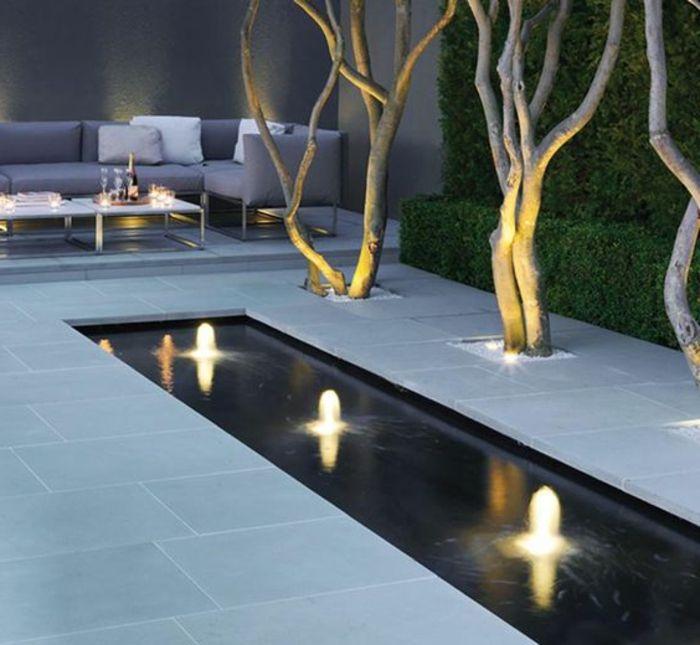 Gartengestaltung Beispiele   ein Wasserspiegel mit Reihen Lichte, schicke Gartenmöbel, Zierbäume