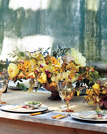 Rustic Centerpiece    At just over a foot tall, this overflowing arrangement is the ideal height for a long, rectangular table.  Along with the blooms and foliage found in the bouquet, the large vessel features Cymbidium, Masdevallia, and Miltonia orchids, plus yellow tree peonies and garden roses. Smaller terra-cotta pots filled with Cymbidium and Masdevallia varieties