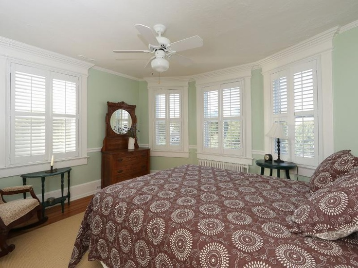 shutters seafoam green walls and brown accents make this bedroom