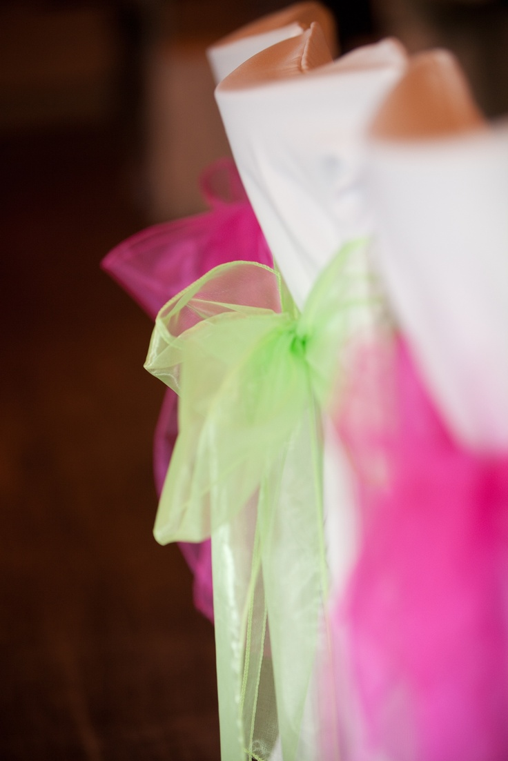 Limeade and fuschia pink organsa chair bows, complete a bright coloured wedding or celebration on white chair covers.  From www.fuschiadesigns.co.uk.