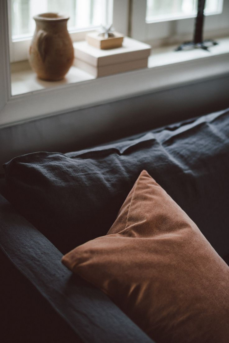 moody scandinavian shades are our jam | dark grey linen sofa | chestnut / rust coloured velvet cushion adds further texture | seen here an IKEA Karlstad sofa with a Bemz Loose Fit Urban slipcover in Medium Grey Rosendal linen and a cushion in Chestnut Malmen velvet