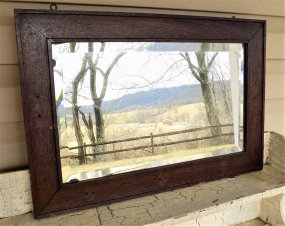 Antique Beveled Mirror, Wood Framed Mirror, Rectangle Beveled Glass and Frame Measures 24 5/8 wide and 16 5/8 tall, frame it 5/8 thick. Glass measures 19 5/8 long and 11 5/8 tall.  Nicely beveled glass mirror inside a simple wood frame. Rustic appeal, aged well, and would make a wonderful addition to your decorating style. Heavy and beautiful. Two older pieces of hanging hardware on back to use.  Darker wood stain with small holes where there was probably decorative hardware installed but…