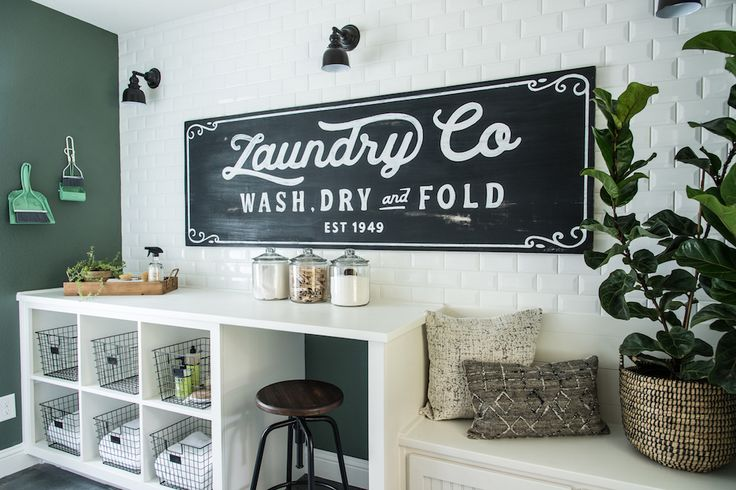 To make the laundry room really stand out we decided to design and paint a laundry room mural on the main wall. We also added a built-in folding station and carried the same green from the kitchen island into this space.