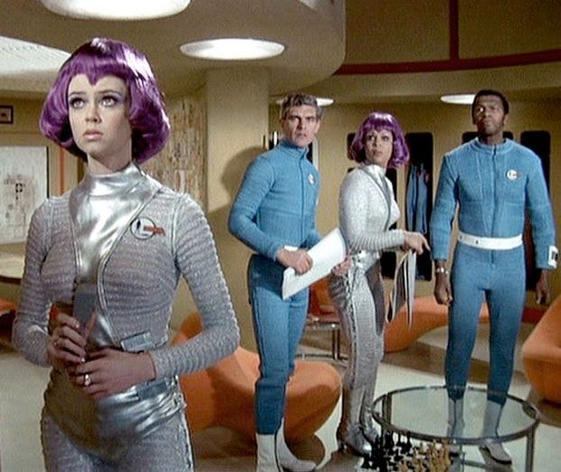 "UFO (1970-1971, ATV, UK; theme by Barry Gray). One of the funkiest and coolest TV themes you've never heard of, from a fascinating day-glo British sci-fi series. Good, worthy themes like this never make most of the half-assed clueless TV ""best themes"" lists out there. But, never fear, folks, because you are in MY hands now. (KevinR@Ky)"