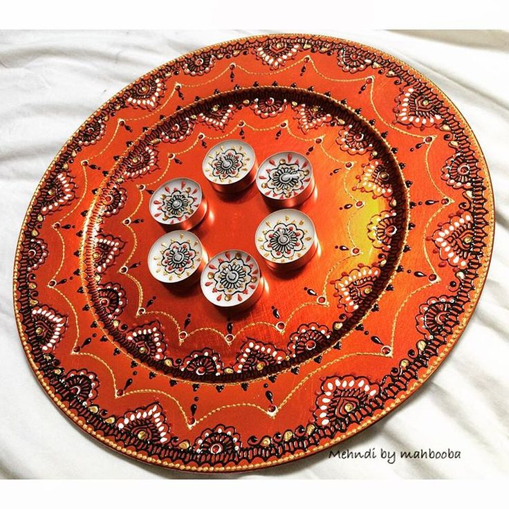 Fiery orange plate with red and gold accent gems, black design and little bits for gold and white detail 🔥🔴🔶◾️ #henna mehndi #deco #plate #candles #HennaArt #MehndiThaals #HennaCandles #bespoke #MehndiArt #love #creative #colour #inspire #instahenna #MehndiByMahbooba