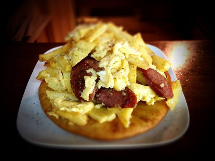 Ομελέτα με πατάτες και λουκάνικο Τρικάλων, σερβιρισμένη πάνω σε τηγανόψωμο Ευβοίας