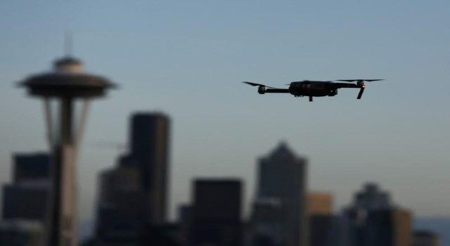 """FILE PHOTO: A drone hovers at a viewpoint overlooking the Space Needle and skyline of tech hub Seattle, Washington, U.S. February 11, 2017.  REUTERS/Chris Helgren  State-of-the-art drones, also known as """"unmanned aerial vehicles"""" (UAVs), will be used at the discretion of the Royal Police For..."""