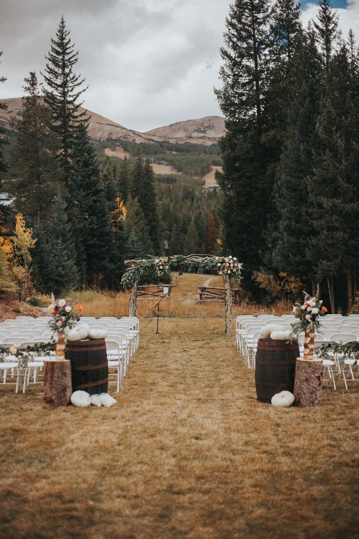 Fall outdoor mountain wedding ceremony with white pumpkins and lush florals | Image by Cork Creative