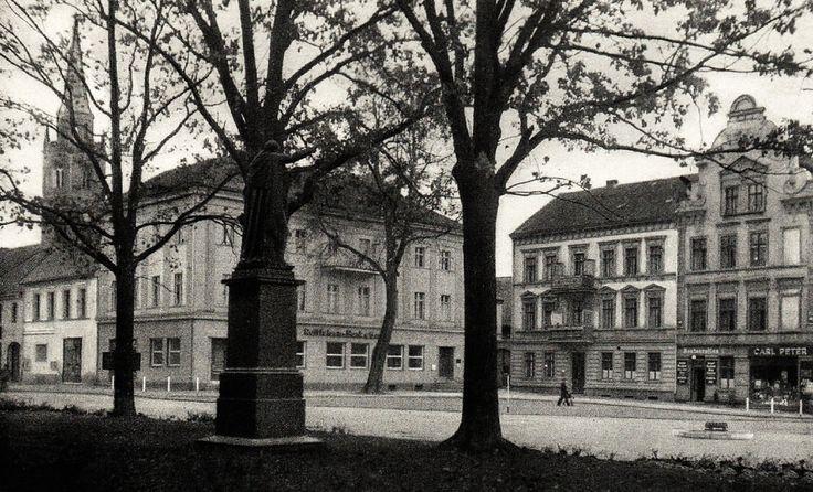 Die Ansichtskarte zeigt den Königsplatz in Gumbinnen (eigentlich Friedrich-Wilhelmplatz, aber einfach auch nur Markt genannt). Im Vordergrund kann man das Standbild des verehrten preußischen Königs Friedrich Wilhelm I. erkennen. Am linken Bildrand sieht man den Turm der Altstädtischen Kirche. Ansichtskarte 1943.