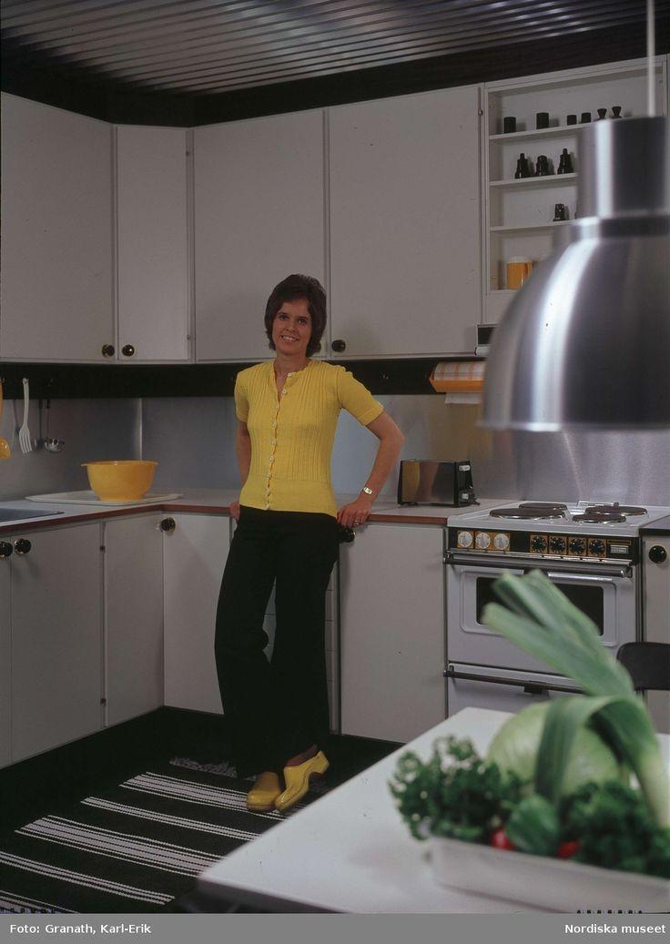 DigitaltMuseum - Kvinna klädd i gul jumper och gula träskor, lutar sig mot arbetsbänk i kök. På bänken en gul plastbunke.