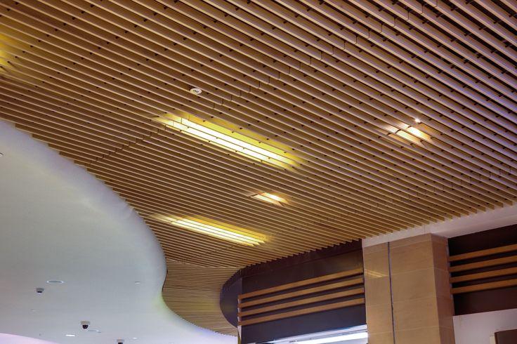 """Los cielos rasos Woodlines HunterDouglas® estan conformados por paneles metálicos que pueden ser fabricados en los paneles Baffle, """"U"""", y Timberline, estos paneles son enchapados en madera natural 0,4 mm de espesor y de largo máximo 5,0 metros."""