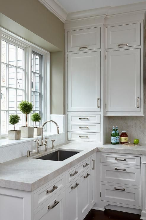 Crisp white shaker cabinets go to the ceiling in this white kitchen and create a spacious feel, while white herringbone tiles accent a sink backsplash complimenting light gray quartz countertops.