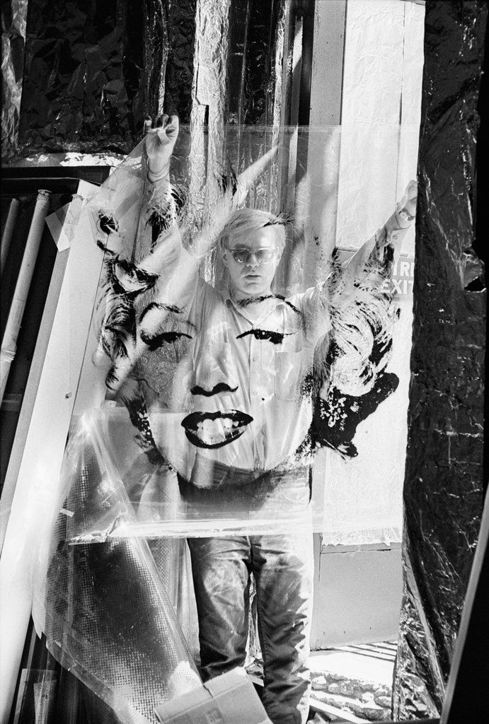 """Andy Warhol with an unrolled acetate of """"Marilyn"""" in his studio """"the Factory"""" in 1964. Original photograph taken by Gene Korman in 1953"""
