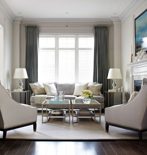 Elegant living room, with light grey sofa and arm chairs with timber trim, dark grey curtains. Glass coffee table and twin side tables with lamp.