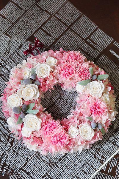 とってもフェミニンなピンクカーネーションとホワイトローズのとってもかわいいリースです。使用する花はすべてプリザーブドフラワーです。 ドアに飾っても、壁に飾っても素敵です。母の日はカーネーションを贈りたいけど毎年同じ・・・という方も、今年はいつもとちょっと違うカーネーションリースを贈りませんか・・・? プリザーブドフラワーリース