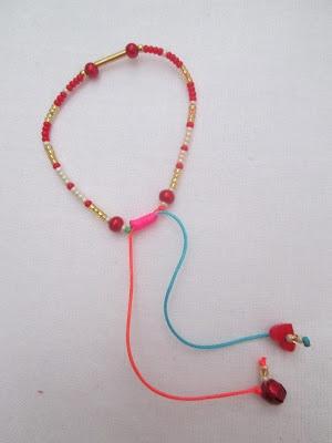 Pulsera Neón y rojo  Materiales: Cordón neón, mostacillas checas, perlas, sonajero metálico, accesorio en acrílico, cuentas y cilindro en oro goldfield  Valor: $10.000