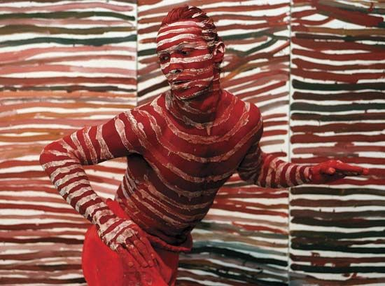 Australian Aborigine: Russell Page performing in front of a painting by Emily Kame Kngwarreye