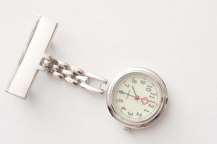 Silver metal nurses fob watch with blank name tag and chain lying diagonally on…