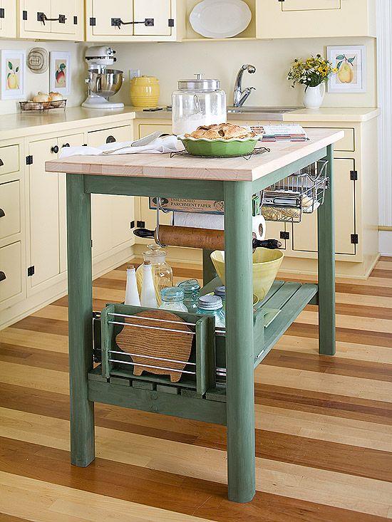 Maravilhosa organização. Com muito espaço aberto para armazenamento e aramados  para manter utensílios de cozinha organizados, esta ilha é muito prática nesta pequena cozinha. Um verde tranquilo funciona bem com armários e pisos de madeira amarelos pálidos.