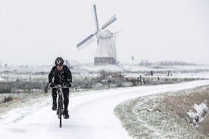 Winter doet intrede in noorden (fotoserie) -  Een fietser in het winterse landschap van de Glimmense polder, in Groningen. Op de achtergrond De Witte Molen uit 1892 aan het Noord-Willemskanaal. beeld ANP