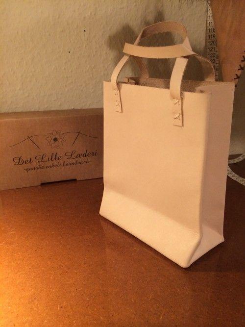 Sød og opsigtsvækkende papirsbærepose, ikke i papir, men en kernelæderbærepose. Håndsyet og håndskåret. Brug tasken som en almindelig taske - til alle de der småting, som ikke kan være i din pung.