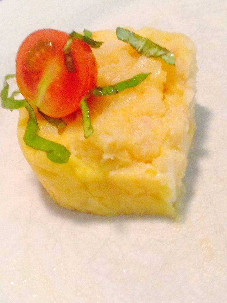 Una deliciosa tortilla de patata con un tomate cherry y albaca