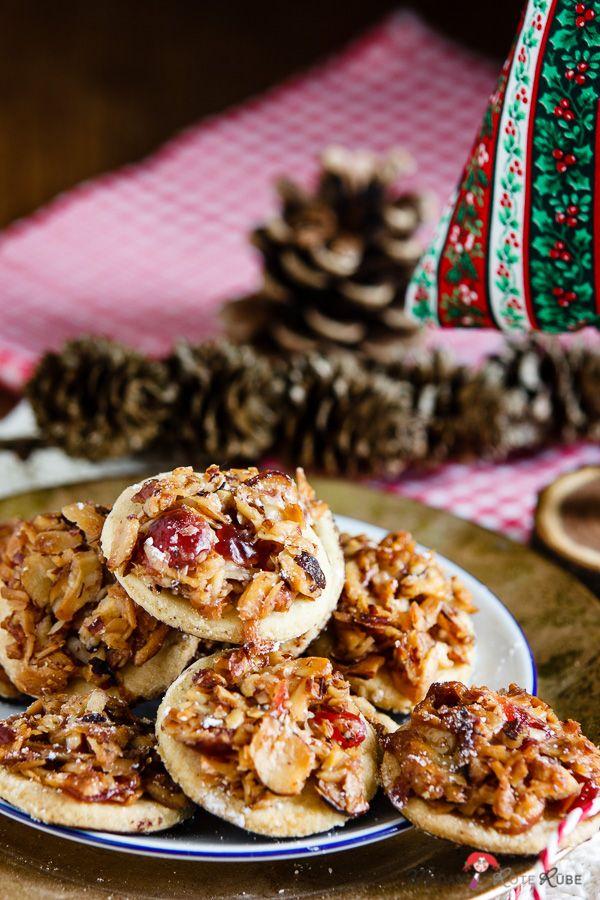 Mandeln, Haselnüsse, Honig und kandierte Kirschen, direkt auf einem mürben Plätzchen mitgebacken, abgekühlt mit einem Füßchen liebevoll getunkt in Zarbitterschokolade.