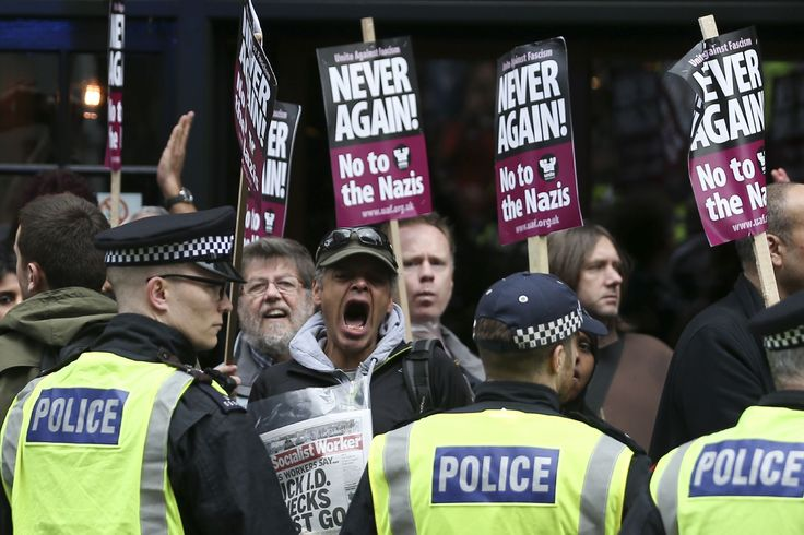 La police britannique encercle des militants équipés de pancartes lors d'une contre-manifestation organisée par le groupe Unite Against Fascism en réponse à des marches d'extrême droite des groupes British Defense League et Britain First dans le centre de Londres. Ces marches surviennent après l'attentat terroriste du 22 mars sur le Parlement britannique.