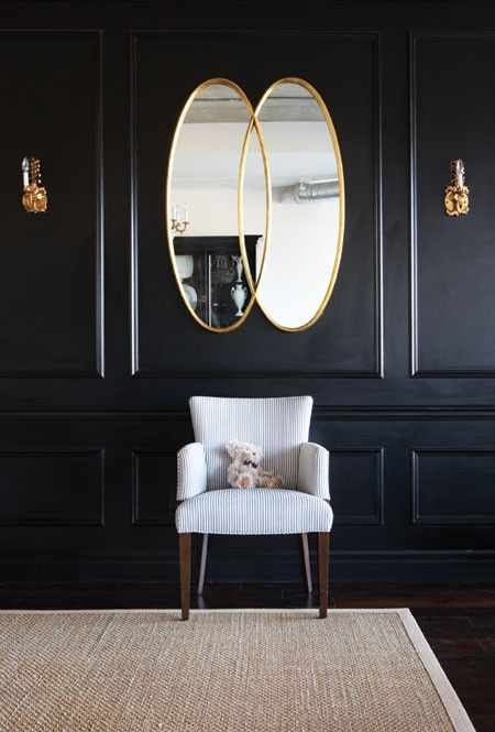 Dark Drama: Black & Gold. Function meets comfort in this historical design. A sleek shade of ebony covers the walls and delicate panelling for a sophisticated look. Gold accents and a vintage version of a classic club chair offer contrast in this dark space. Photographer: Michael Graydon