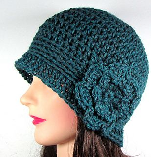 This crocheted cloche hat or beanie features a band in a contrasting stitch and an attached crochet flower.