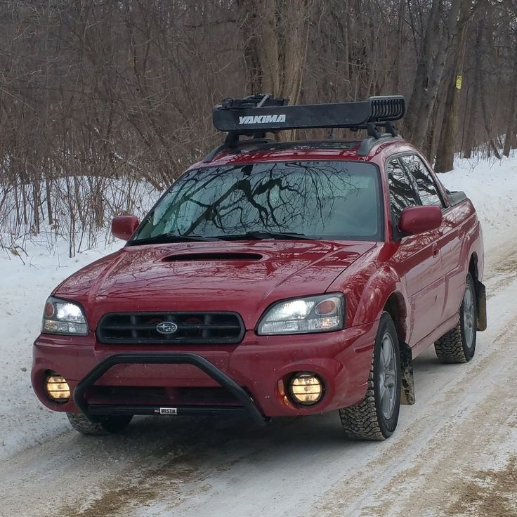 Red subaru baja with blacked out grille bumper bar and roof rack